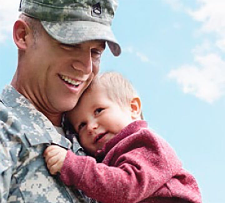 Man in military uniform holding child